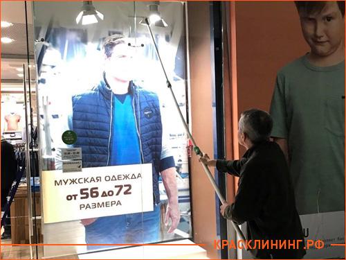Клинер моет витрину в магазине одежды