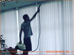 Мужчина с пылесосом чистит жалюзи в гостинице